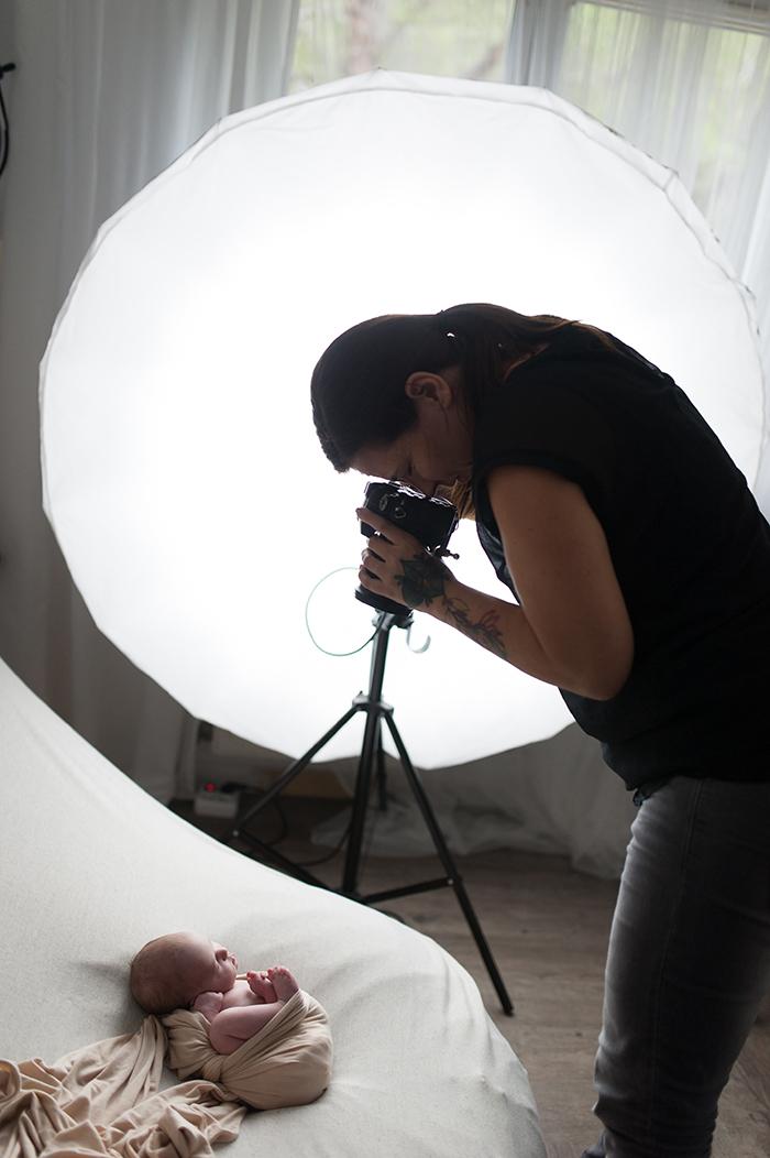 Photographe en pleine séance avec un nouveau-né.