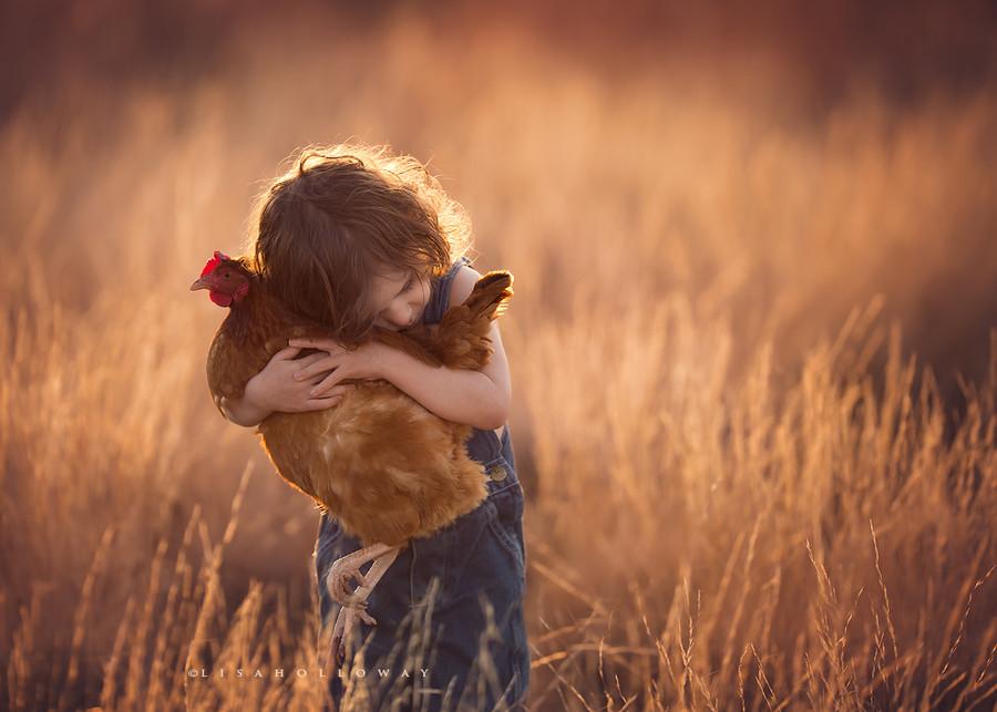 jeune garçon serrant une poule dans ses bras