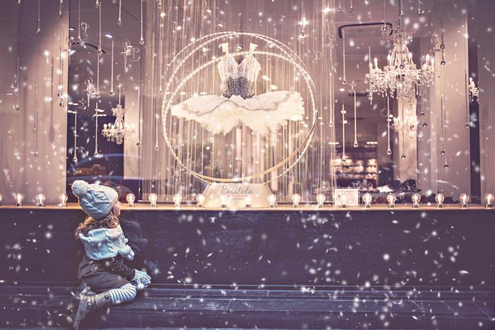 enfant devant une boutique, sous la neige