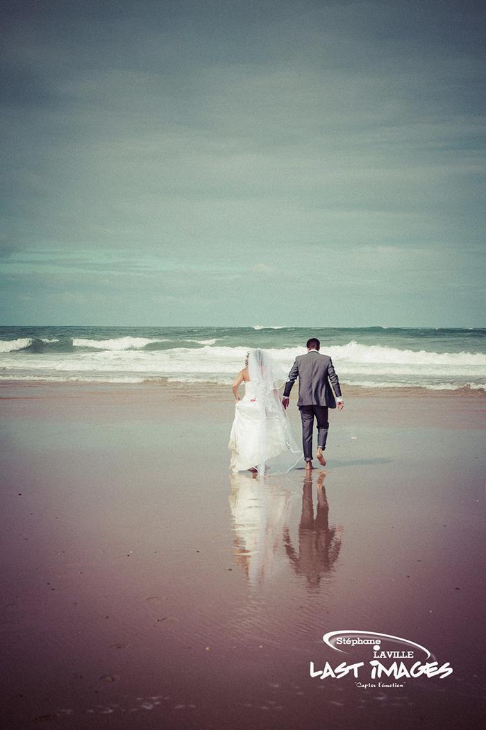 COuple de mariés marchant vers la mer