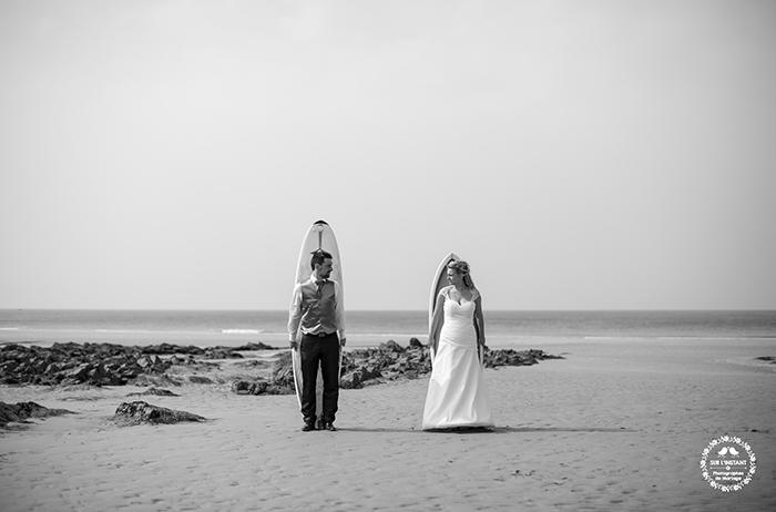 Photo de mariés surfeurs, devant leur planche et la mer