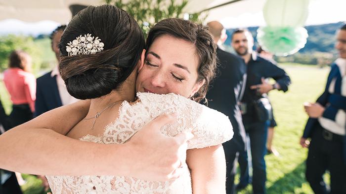photo de mariage : une mariée enlace une invitée