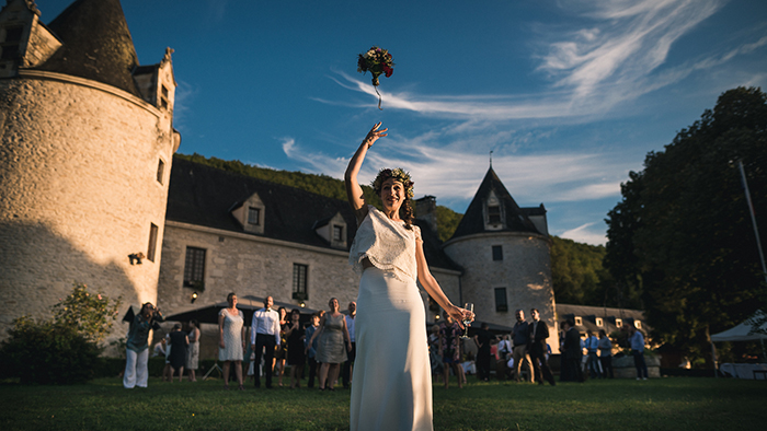 le lancé du bouquet de la mariée devant un château