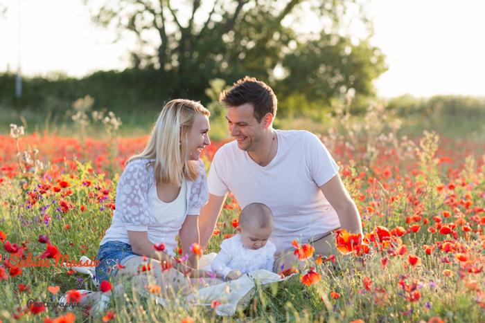 Séance photo d'une famille dans les champs de coquelicots.