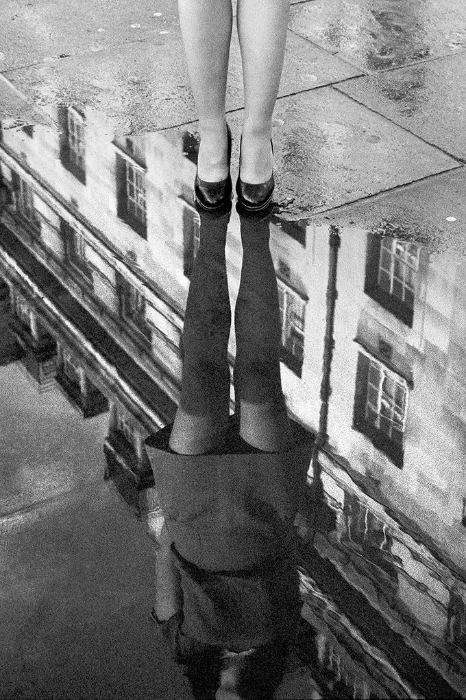 Photo de rue, en argentique, d'une jeune femme et son reflet dans une flaque d'eau. Par Gildas Lepetit-castel