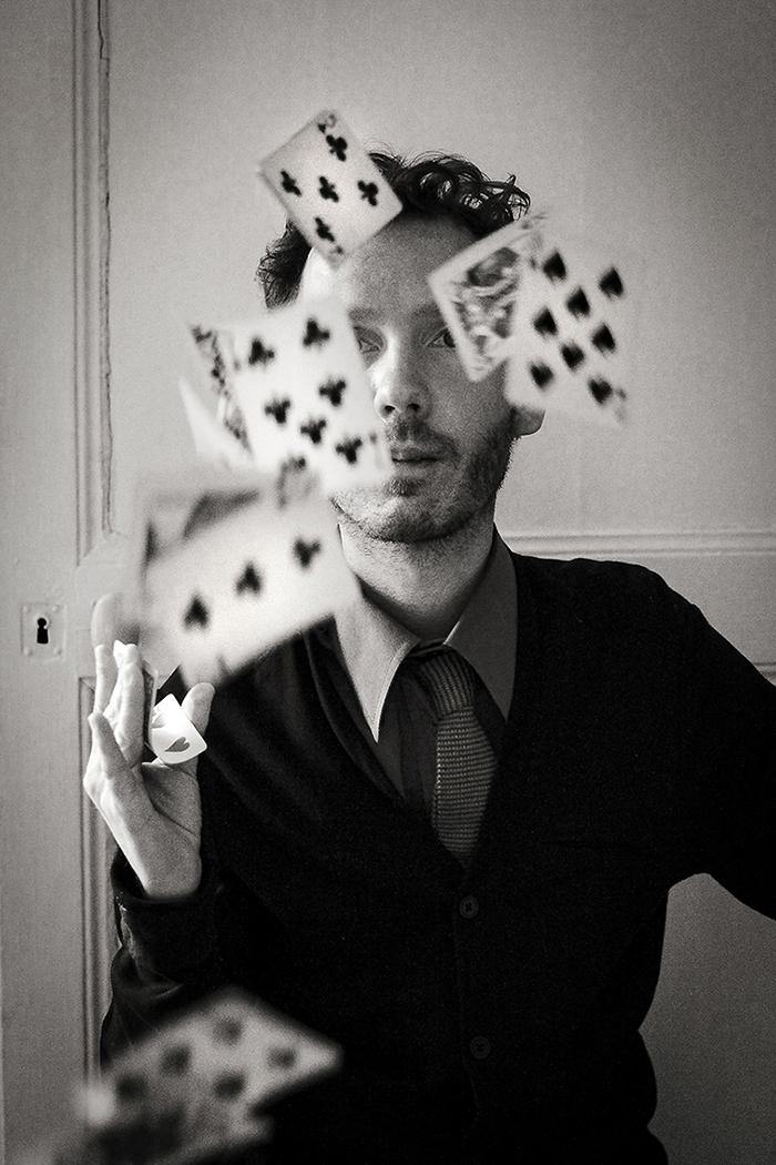 Photographie argentique, un homme, peut-être un magicien, qui joue avec des cartes.