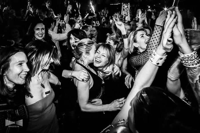 Photographie en noir et blanc : une accolade dans la foule