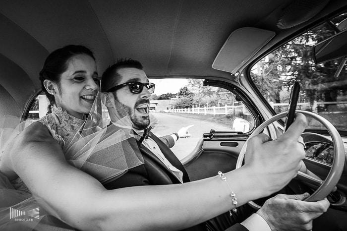 Photographie noir et blanc de mariés dans une voiture