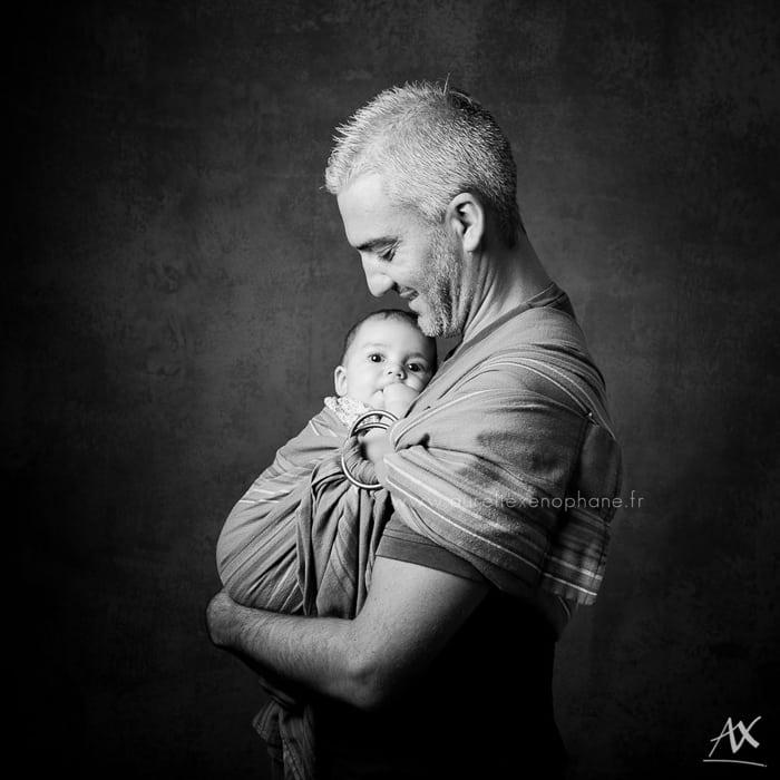 Le portage en écharpe d'un bébé par son papa. Le regard attendri