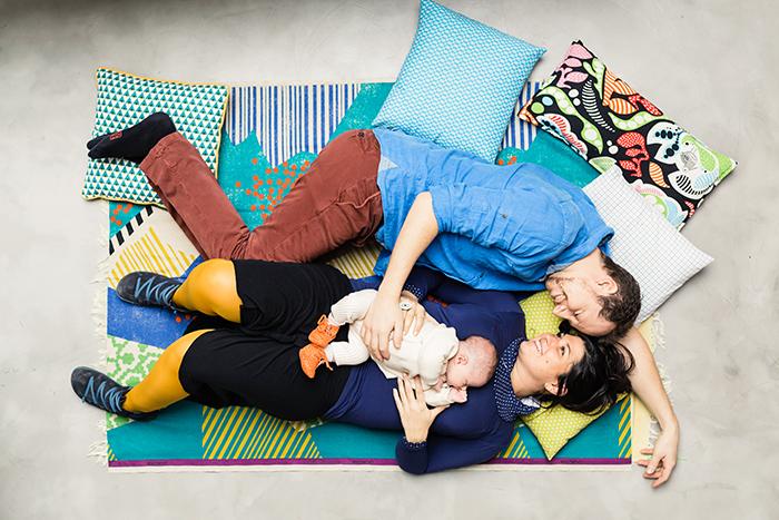 Photo d'une famille allongés sur le canapé avec leur petit bébé dans les bras. Une image tendre de Caroline Vidal.