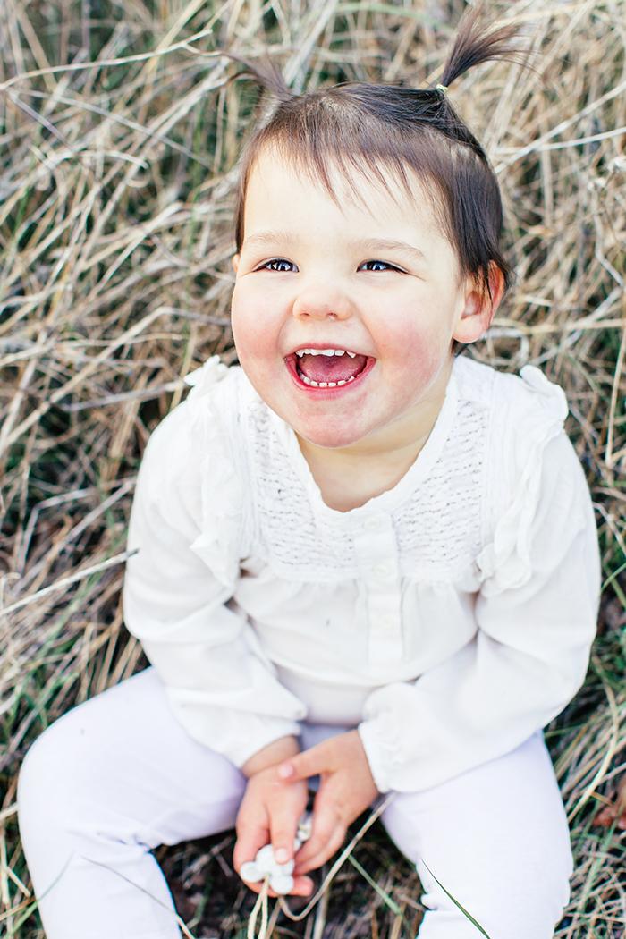 Portrait d'une petite fille qui rigole, vétue de blanc comme pour un baptême.