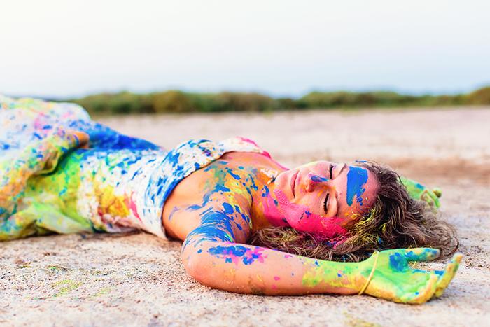 Un portrait colorée d'une jeune femme allongée sur le sol après avoir joué avec de la peinture !
