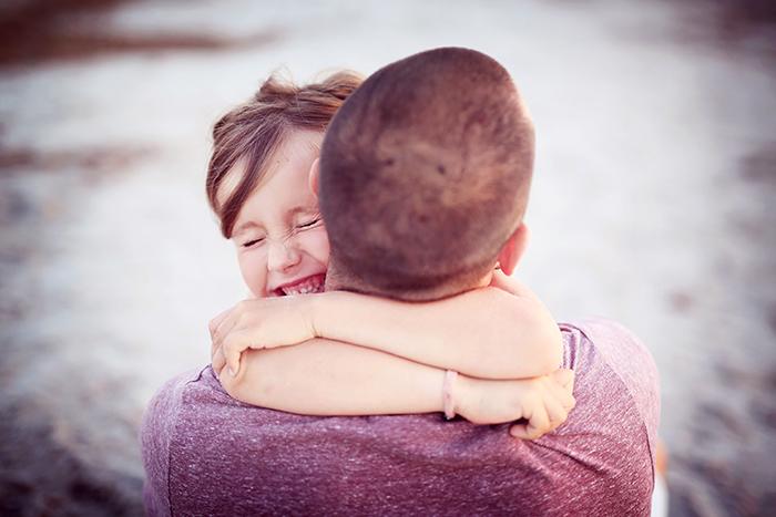 Petite fille qui sert très son papa dans les bras. Ils sont heureux.