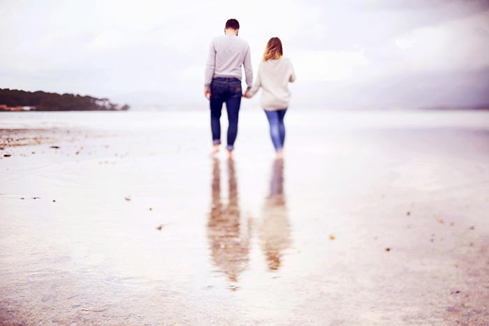 Séance photo de couple au bord de la mer, pendant une journée pluvieuse. Réalisée par Audrey Leguen.