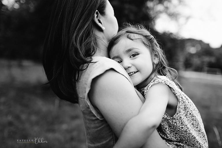 Photographie en noir et blanc, d'une jeune fille dans les bras de sa maman. Elle a un joli regard coquin.
