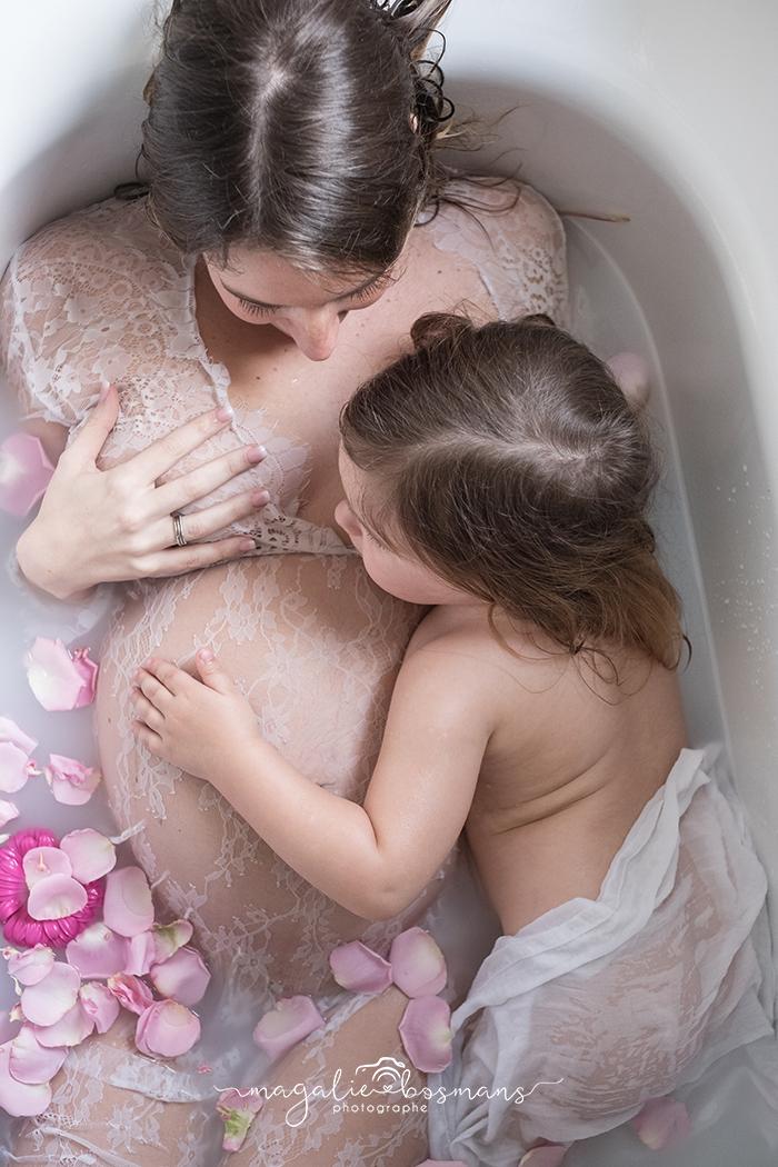 Photographie d'une maman enceinte dans un bain de lait avec sa fille. Par Magalie Bosmans