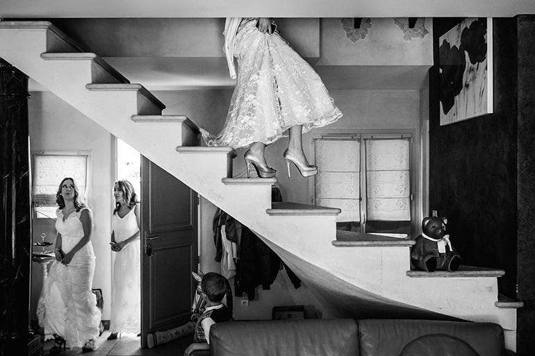 Photo de mariage en noir et blanc : la mariée descend les escaliers.