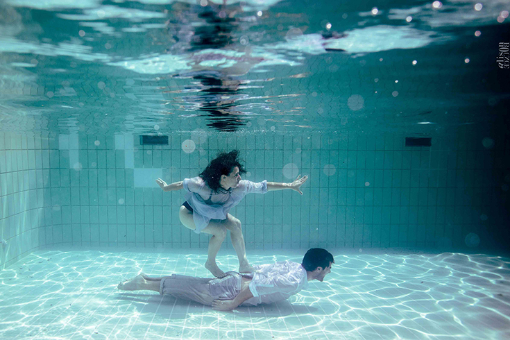 Photographie aquatique, un couple s'amuse en piscine, sous l'eau. Photo artistique d'Alison Bounce.