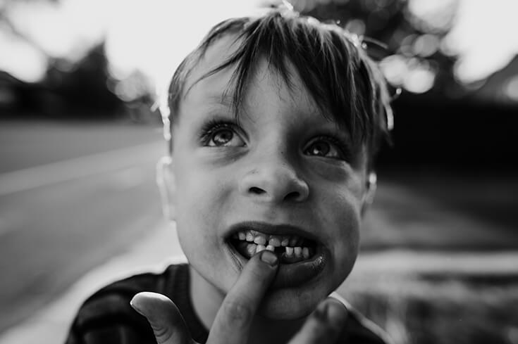 Gros plan d'un enfant en train de réfléchir. Une image noir et blanc, artistique, de Catherine Giroux.