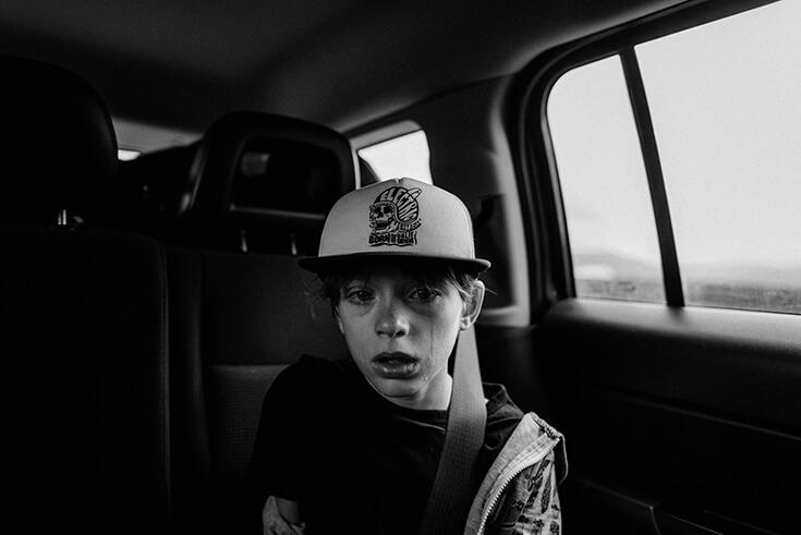 Photo noir et blanc d'une jeune garçon. Il a les larmes aux yeux.