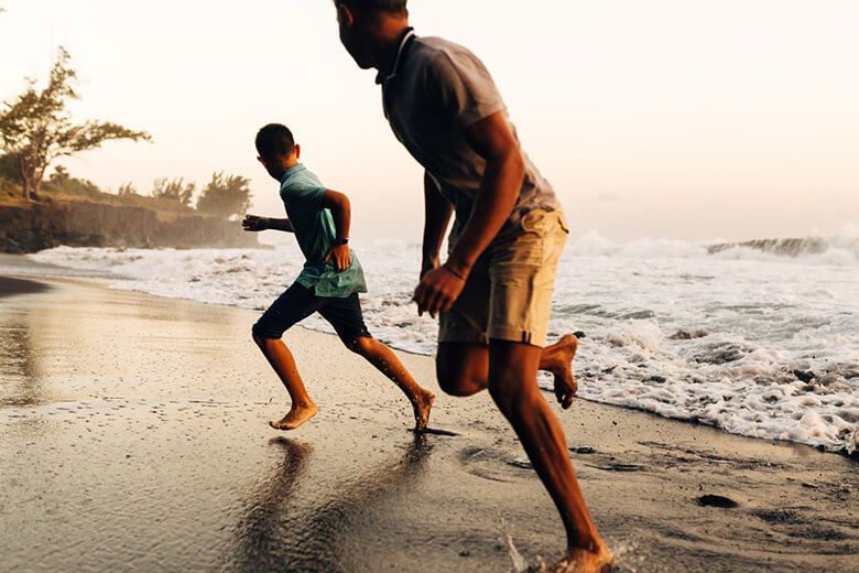 Un homme est son fils courant sur la plage